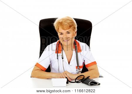 Smile elderly female doctor or nurse sitting behind the desk with bloog preasure gauge