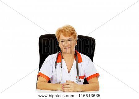 Smile elderly female doctor or nurse sitting behind the desk