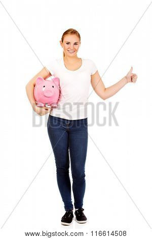 Happy young woman holding piggybank and showing thumb up