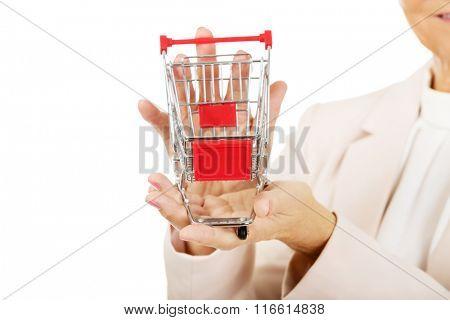 Elderly woman holding small trolley