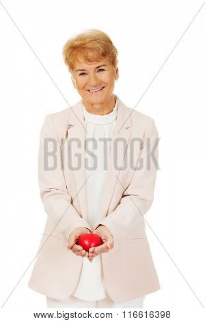 Smile elderly woman holding heart model