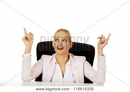 Business woman sitting behind the desk and pointing up for copyspace or something