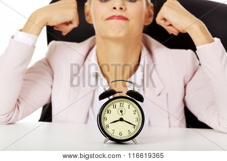 Surprised business woman lsitting behind the desk with alarm clock