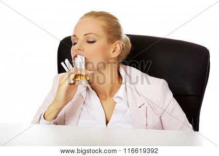 Business woman sitting behind the desk and smelling a few cigarettes