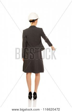 Backview of architect business woman wearing white helmet  pointing down