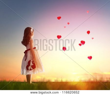 Sweet child girl looking at red balloons. Balloons in shape of heart flying in the sunset sky. Wedding, Valentine, love concept.