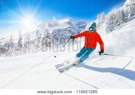 Skier skiing downhill during sunny day in high mountains.
