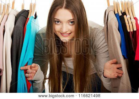 Teen woman between clothes on hanger.