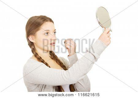 Teen woman applying lipstick looking at mirror.