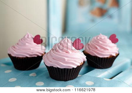 Cupcakes traditional American sweet dessert with red hearts on wooden shelf background