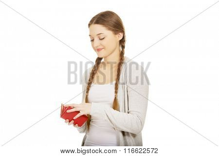 Happy teen woman with a wallet.