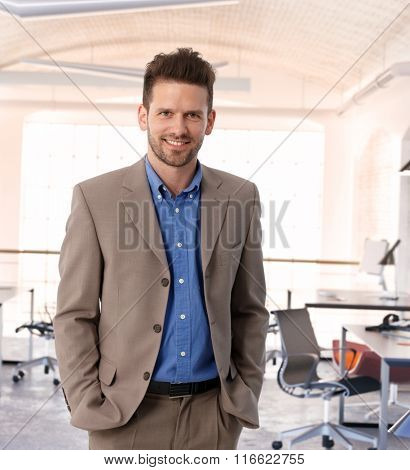 Happy entrepreneur at contemporary office, wearing suit, smiling.
