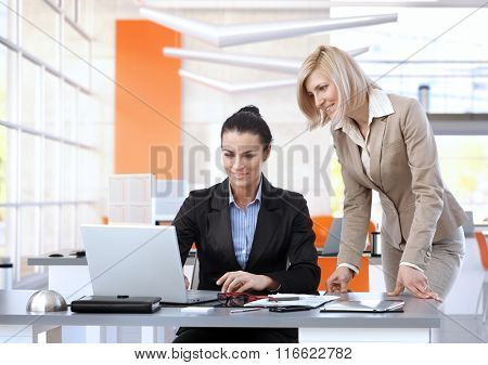 Smiling, attractive, mid-adult caucasian brunette businesswomen working on laptop computer at bright business office desk.