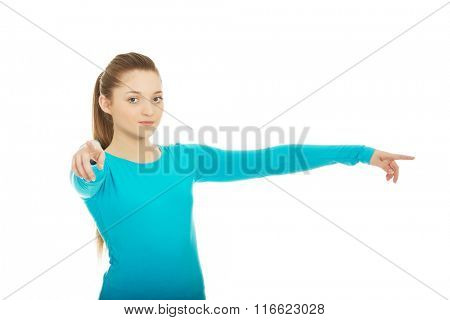 Young woman pointing on you and aside.