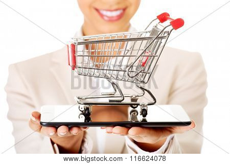 Businesswoman with shopping cart and tablet.