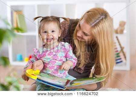 Happy young woman and child girl watching a baby booklet
