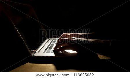 Man working on laptop in dark room
