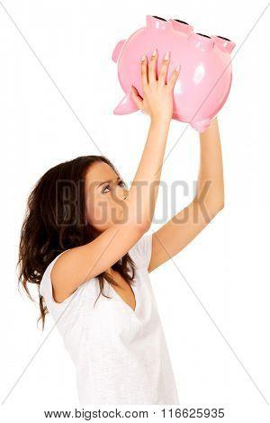 African woman shaking piggybank.