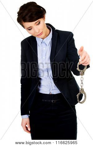 Businesswoman holding metal handcuffs.