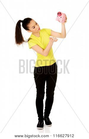 Unhappy woman shaking piggybank.
