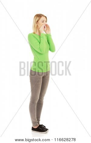 Young woman whispers gossip.