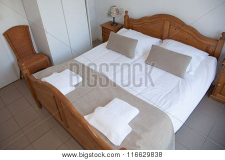 Cheerful Bedroom Interior In Brown And White Color With Bright Red Curtains And Colorful Bedding
