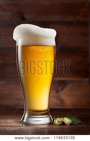 Glass of beer on wooden background with green hop