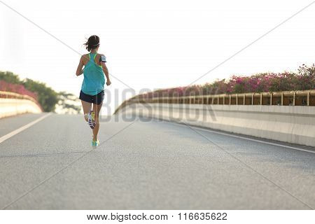 young fitness woman runner running at city road