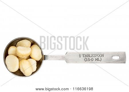 macadamia nuts in a metal measuring tablespoon isolated on white
