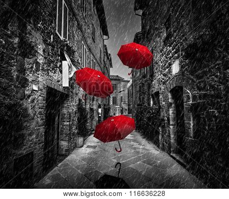 Umbrellas flying with wind and rain on dark narrow street in an old Italian town in Tuscany, Italy.. Black and white with red