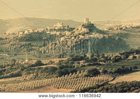 Tuscany countryside landscape with ancient castle, vineyard and green hills, Italy. Vintage sunset