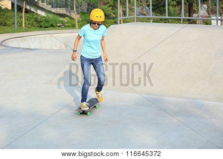 one skateboarding woman riding skateboard at skatepark