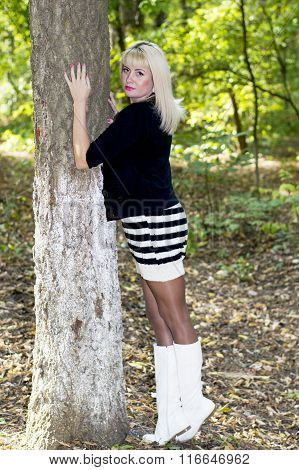 The Beautiful Woman The Blonde Embraces A Tree In Park