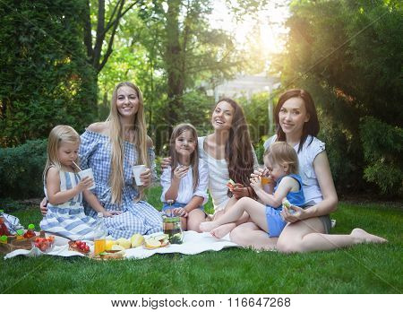 Happy Young Mothers And Daughters Having Picnic In Summer Park