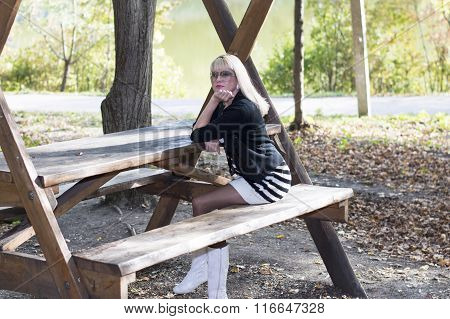 The Blonde In Sunglasses At A Wooden Table At The Lake