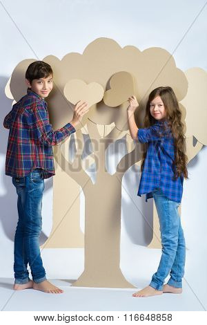 Boy with girl hiding behind cardboard tree and holding a heart. Love concept