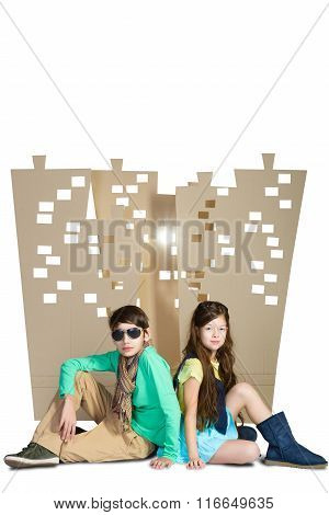 Love concept. Stylish boy and girl sitting on background of cardboard city. isolate white