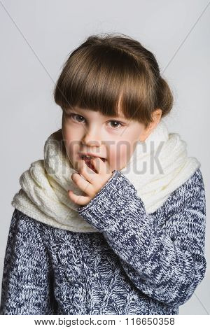 girl holding a finger in the mouth. Close up female face portrait