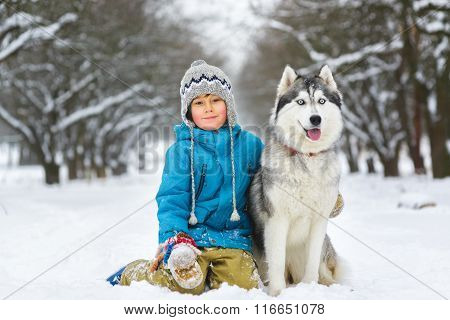 happy boy hugging dog or husky outdoors in winter day