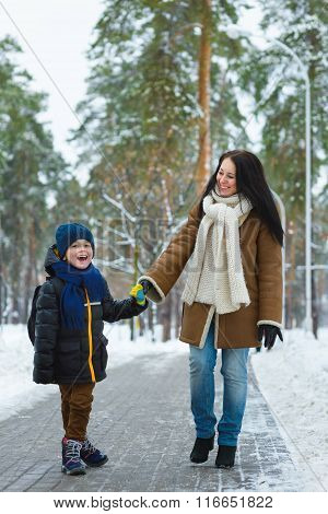 Happy family in winter clothing. Smiling mother and son walk at the park