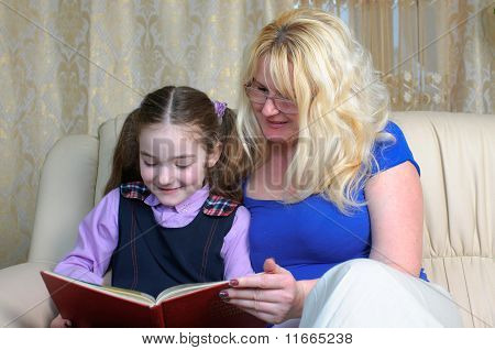 Little School Girl And Mother Doing Homeworks