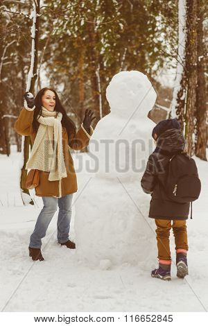 Happy family in warm clothing. Smiling mother and son play snowballs next to a snowman outdoor. The