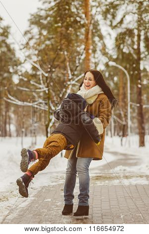 Happy family in winter clothing. laughing Mother and son playing fun game outdoor