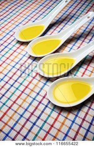 Olive oil in a mall white spoons on a tablecloth