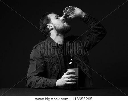 Young Man Is Drinking Alcohol From A Wineglass , Bottle On The Table