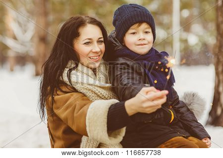 happy mother and cheerful son keep a sparklers or bengal fires outdoor