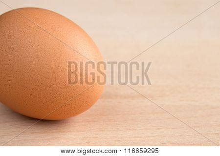 Single brown egg on a wooden chopping board