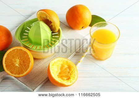 Citrus Fruits With Juicer On A White Wooden Table