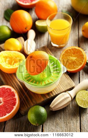 Citrus Fruits With Juicer On A Brown Wooden Table