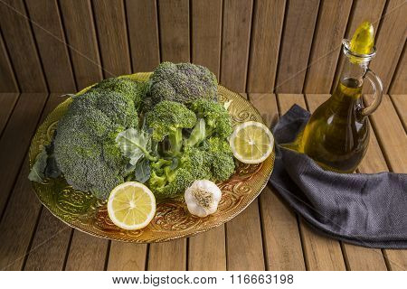 Bunch of fresh green broccoli and olive oil on wooden background.